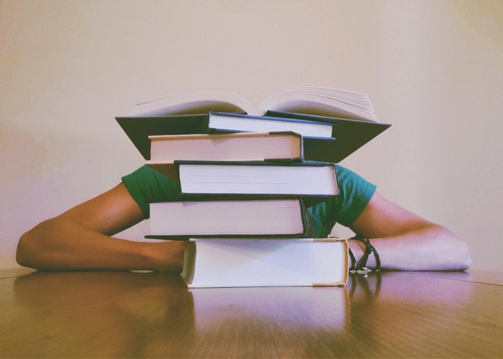 Person versunken hinter einem Stapel Schulbüchern
