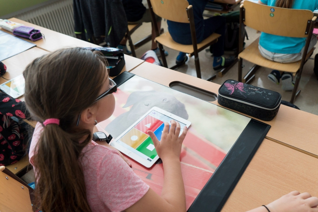 Edutainment in der Schule: Kind lernt mit iPad