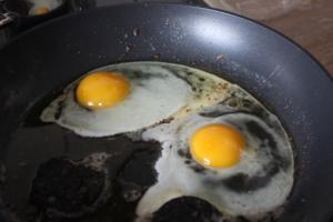Bratet die Eier zu Spiegeleiern an