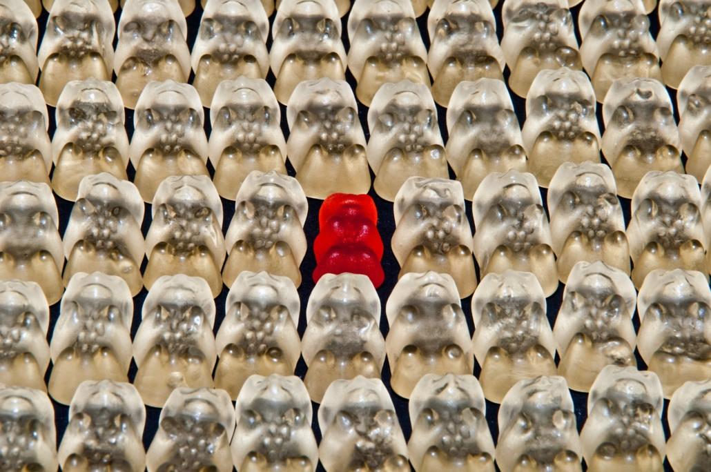 Ein rotes Gummibärchen unter vielen weißen